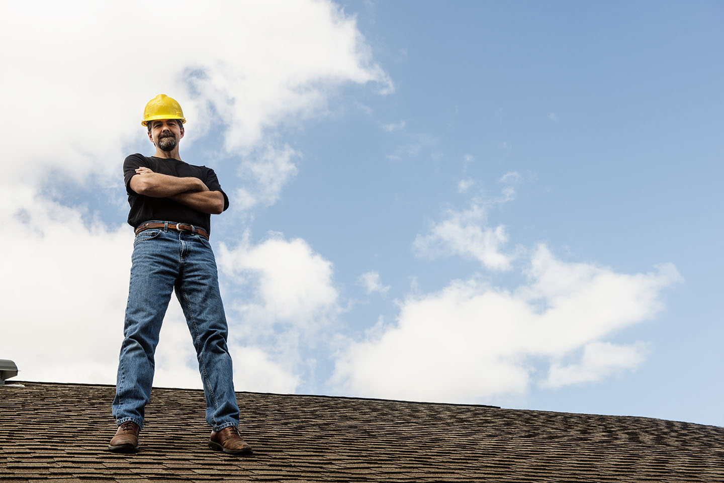This is a horizontal, color photograph of a male construction worker standing on top of a shingled room. White clouds and blue sky behind him provide copy space.